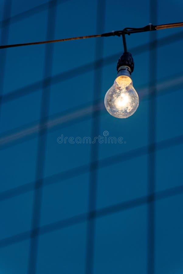 Fermez-vous vers le haut de la photo de l'ampoule sur le fond de fenêtre de bâtiment images stock
