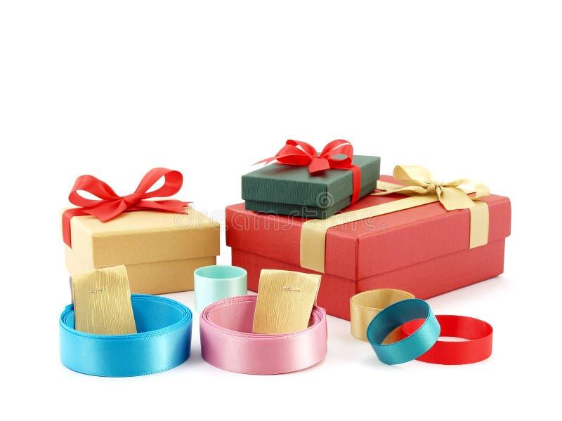Fermez-vous vers le haut de la pile des rubans colorés de petit pain avec des courroies de label de papier d'or et des boîte-cade photo stock