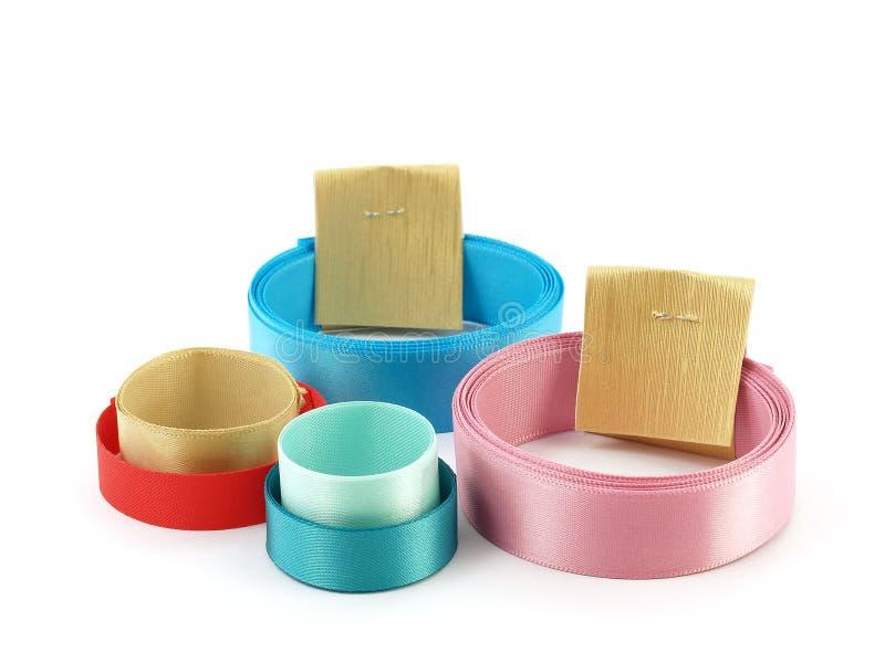 Fermez-vous vers le haut de la pile des rubans colorés de petit pain avec des courroies de label de papier d'or d'isolement sur l image stock