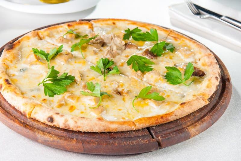 Fermez-vous vers le haut de la pizza gastronome avec les champignons blancs de Gorgonzola et de porcini décorés des feuilles de p image libre de droits
