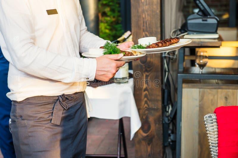 Fermez-vous vers le haut de la portion de serveur au restaurant pendant un banquet ou tout autre événement approvisionné Concept  photo libre de droits
