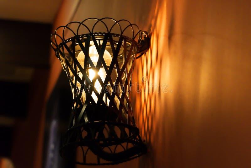 Fermez-vous vers le haut de la rétro lampe de mur, ampoule décorative à l'arrière-plan orange-foncé photo libre de droits
