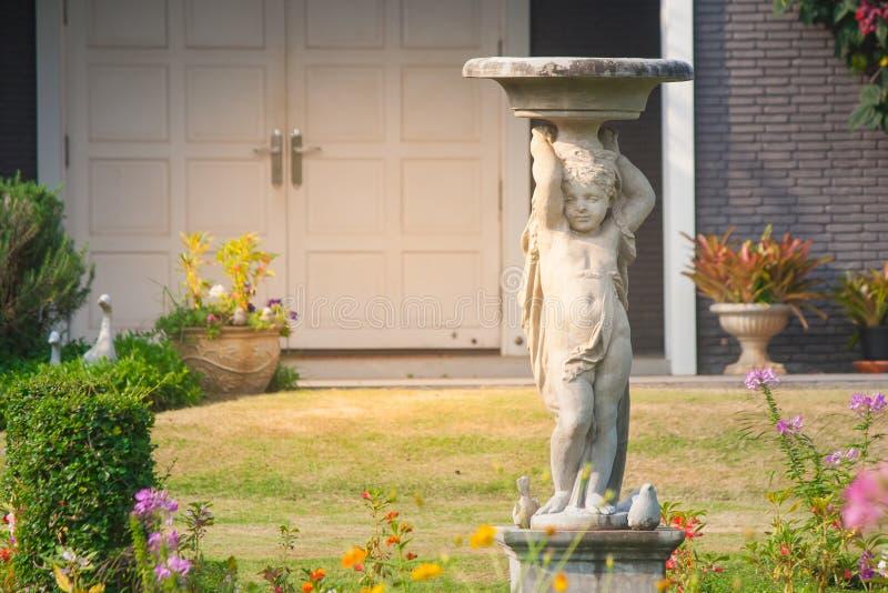 Fermez-vous vers le haut de la sculpture ou de la statue blanche se tenant sur le jardin extérieur pour la décoration photos stock