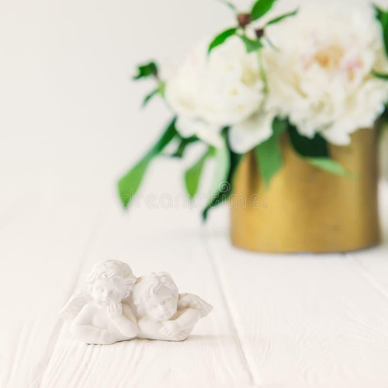 Fermez-vous vers le haut de la statuette de deux petits beaux anges antiques du gypse sur la table en bois blanche avec le bouque photo libre de droits