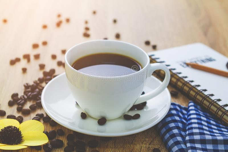 Fermez-vous vers le haut de la tasse de café blanc sur la table en bois brune près de la fenêtre images stock