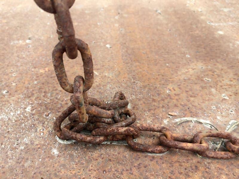 Fermez-vous vers le haut de la terre sale de vue extérieure et de la couleur brune, d'une chaîne rouillée antique placée au sol photographie stock libre de droits