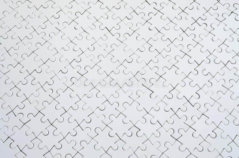Fermez-vous vers le haut de la texture d'un puzzle denteux blanc en état assemblé Vue supérieure Beaucoup de composants d'une gra photographie stock