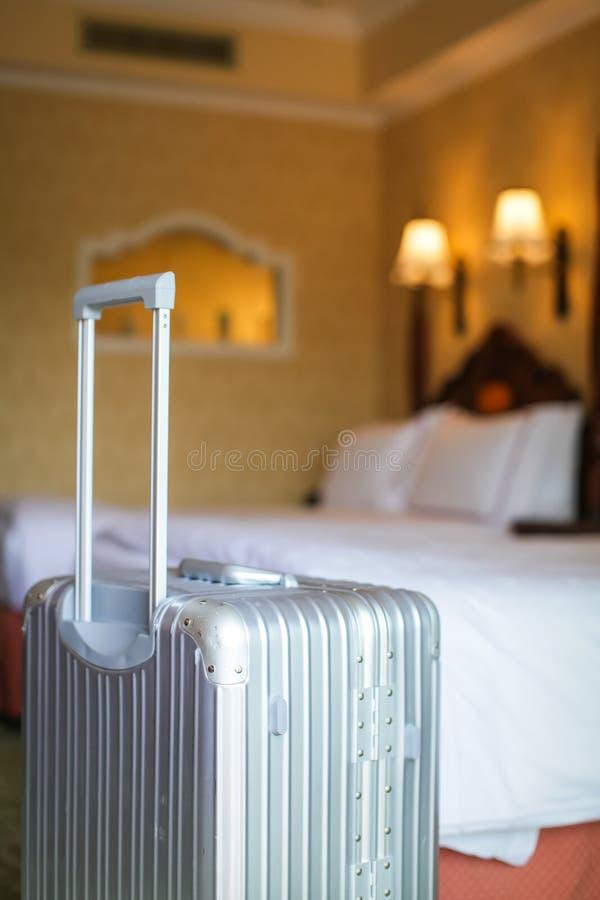 Fermez-vous vers le haut de la valise argentée grise de voyage est dans une chambre d'hôtel inoccupée et il y a la couverture de  photo libre de droits