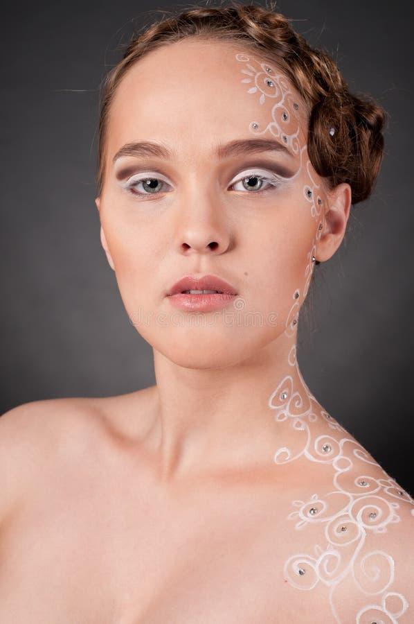 Fermez-vous vers le haut de la verticale de la belle fille avec l'art de visage photo stock