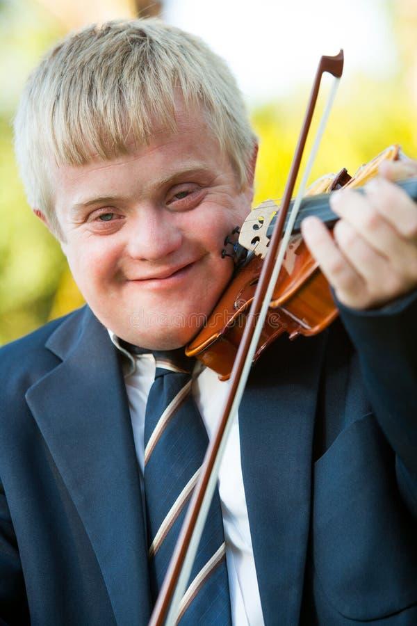 Fermez-vous vers le haut de la verticale du garçon handicapé avec le violon. image libre de droits