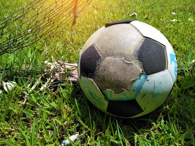 Fermez-vous vers le haut de la vieille larme de boule sur la pelouse, équipement pour le sport du football illustration libre de droits