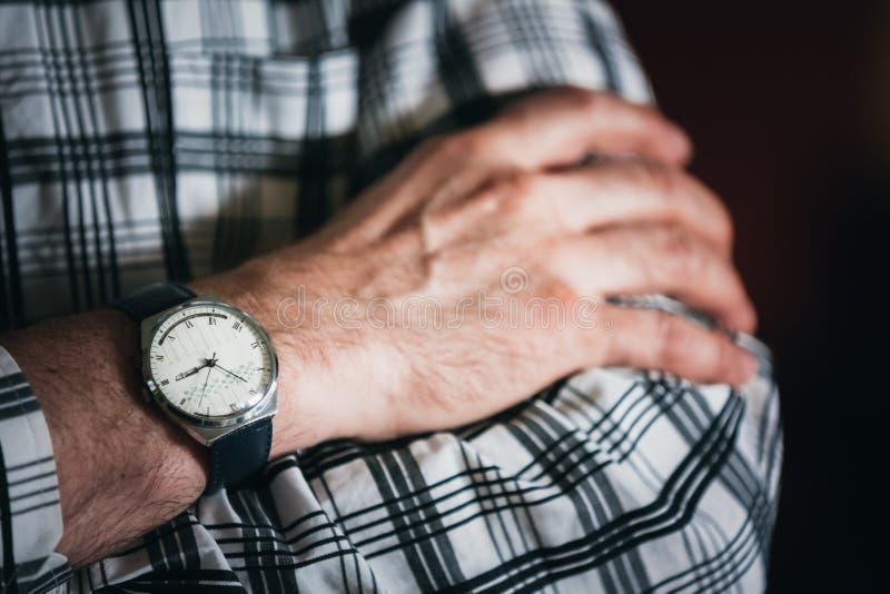 Fermez-vous vers le haut de la vieille montre de vintage sur la main de l'homme rayé image libre de droits