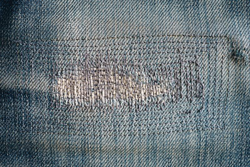 Fermez-vous vers le haut de la vieux texture et fond de denim de jeans de correction photos stock