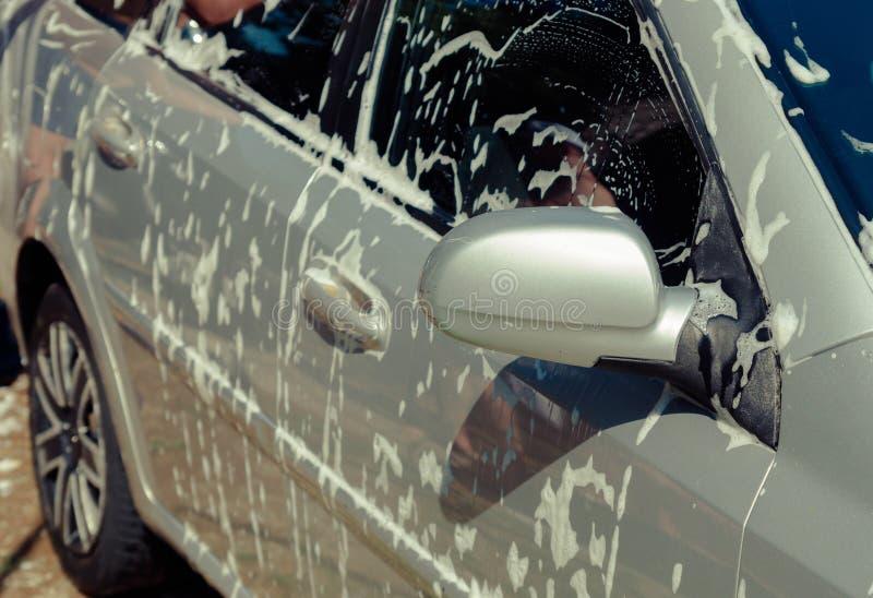 Fermez-vous vers le haut de la voiture de nettoyage avec l'eau et la mousse photos libres de droits