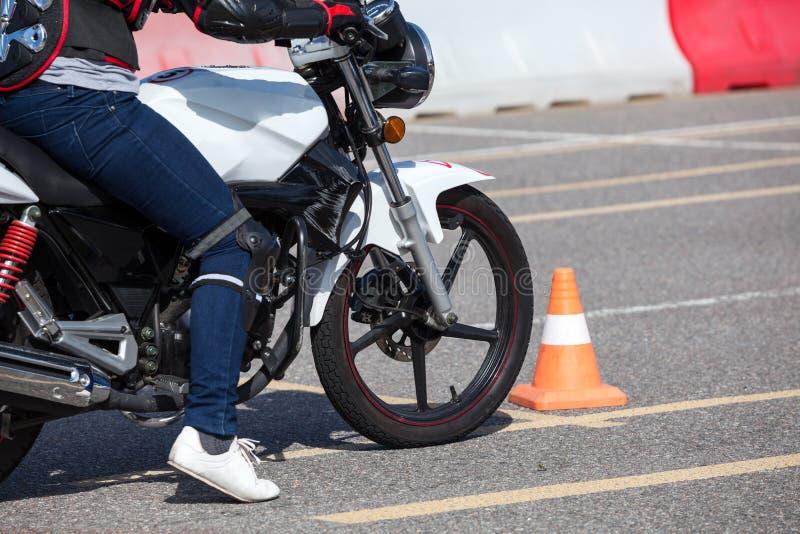 Fermez-vous vers le haut de la vue à la motocyclette de formation avec la personne pratiquant sur le polygone d'essai de véhicule image stock