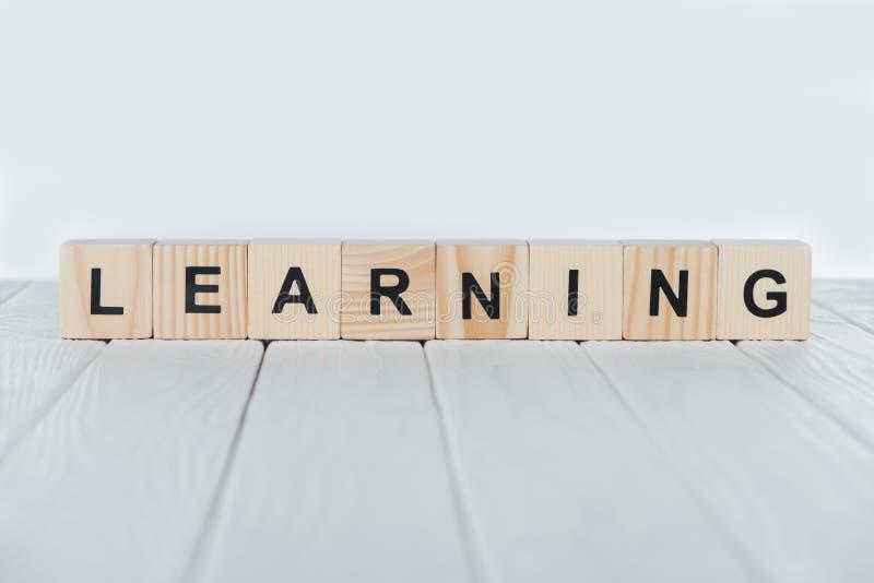 fermez-vous vers le haut de la vue d'apprendre le mot faite de cubes en bois sur le blanc photographie stock libre de droits