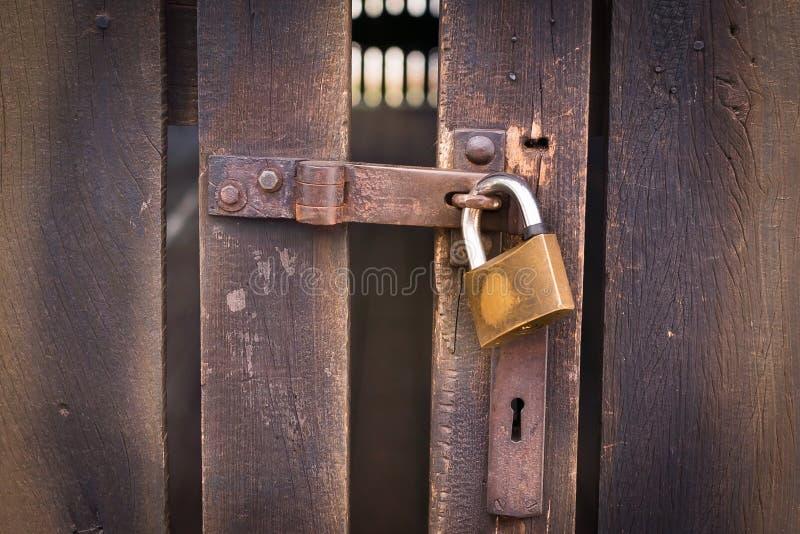 Fermez-vous vers le haut de la vue d'un cadenas et d'une vieille porte en bois image stock