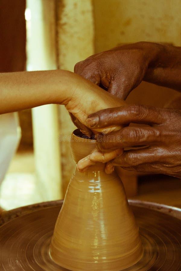 Fermez-vous vers le haut de la vue d'un potier principal enseignant un enfant sur la façon dont faire un broc sur une roue de pot photo stock