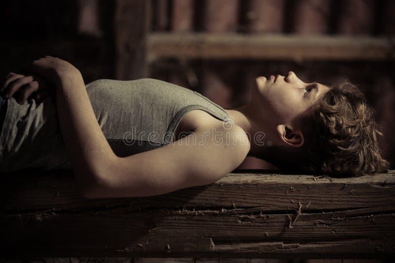 Fermez-vous vers le haut de la vue de côté du garçon s'étendant sur le banc en bois photos libres de droits