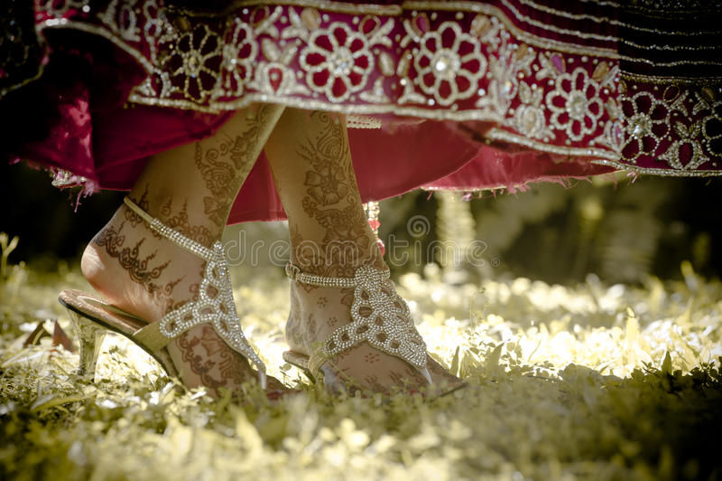 Fermez-vous vers le haut de la vue de la jeune mariée indoue peinte des pieds dansant dans le jardin photographie stock