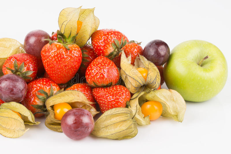Fermez-vous vers le haut de la vue de la pomme verte avec le physalis orange, les raisins pourpres et les fraises rouges images stock