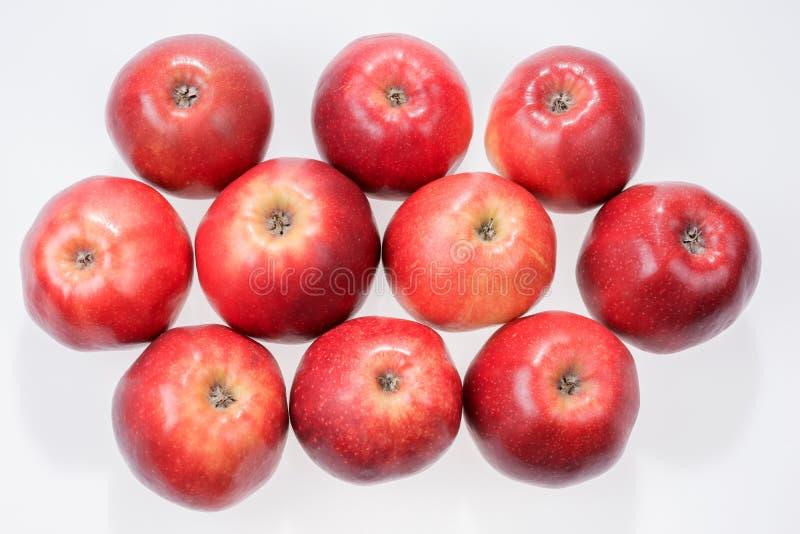 Fermez-vous vers le haut de la vue de quelques pommes rouges d'isolement sur le blanc photo stock