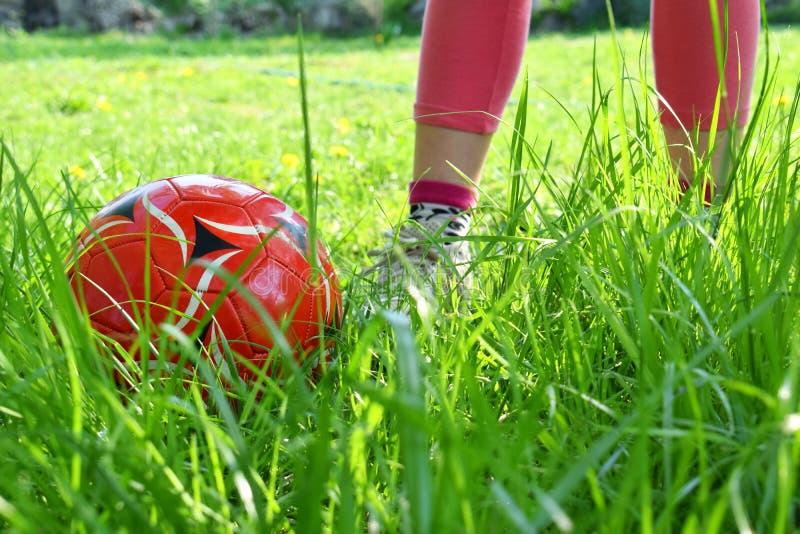 Fermez-vous vers le haut de la vue des jambes du ` s de fille et de la boule rouge sur l'herbe verte Enfants jouant le concept du images stock