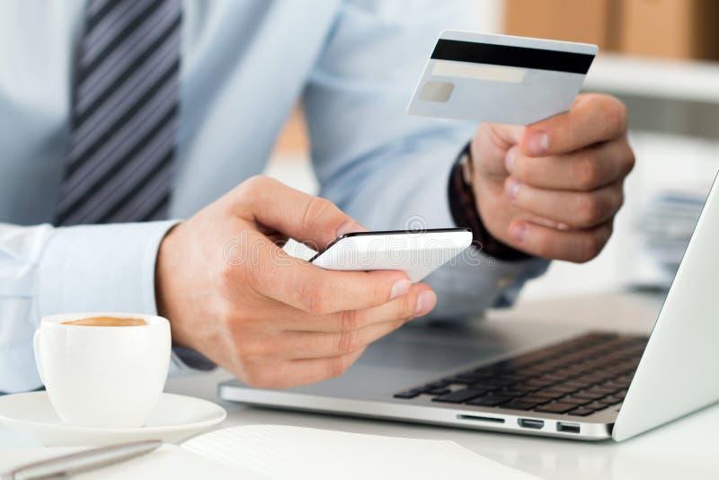 Fermez-vous vers le haut de la vue des mains d'homme d'affaires tenant la carte de crédit et le makin photographie stock libre de droits