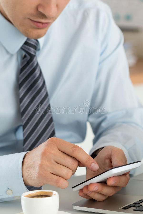 Fermez-vous vers le haut de la vue des mains d'homme d'affaires tenant le téléphone intelligent images stock
