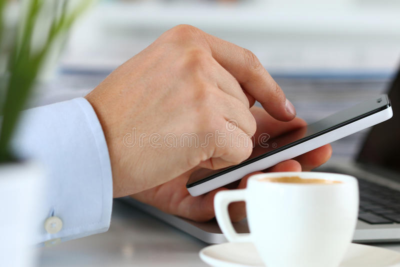 Fermez-vous vers le haut de la vue des mains d'homme d'affaires tenant le téléphone intelligent image stock