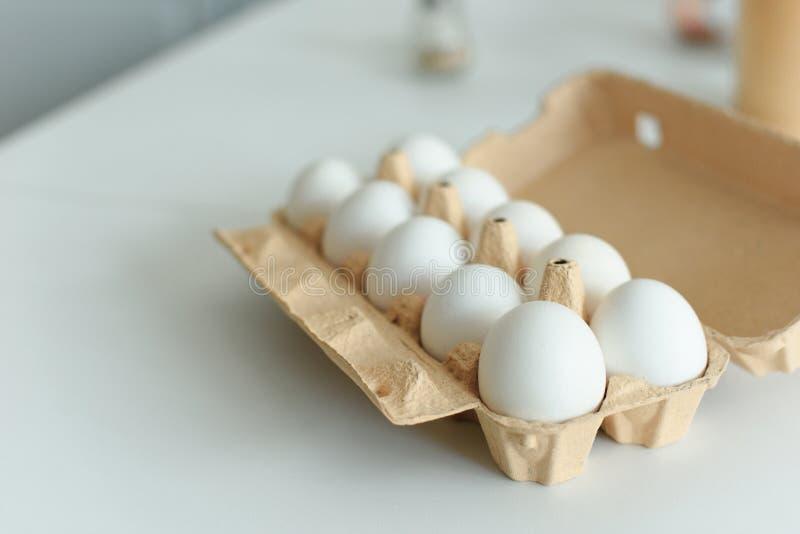 fermez-vous vers le haut de la vue des oeufs crus de poulet dans la boîte sur le dessus de table image libre de droits