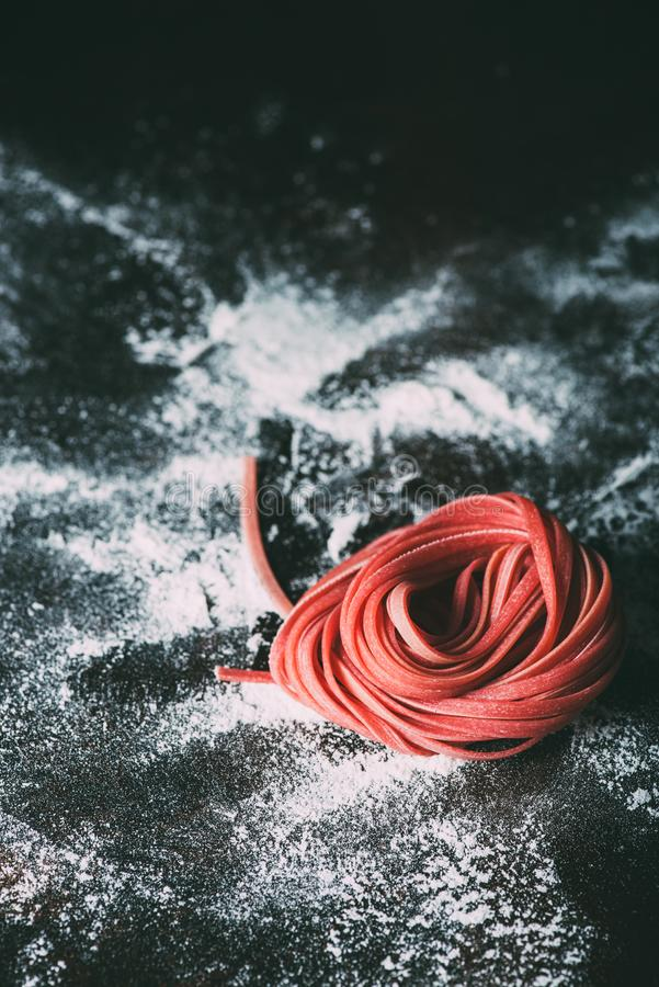fermez-vous vers le haut de la vue des pâtes crues rouges de tagliatelles sur la table couverte photo libre de droits