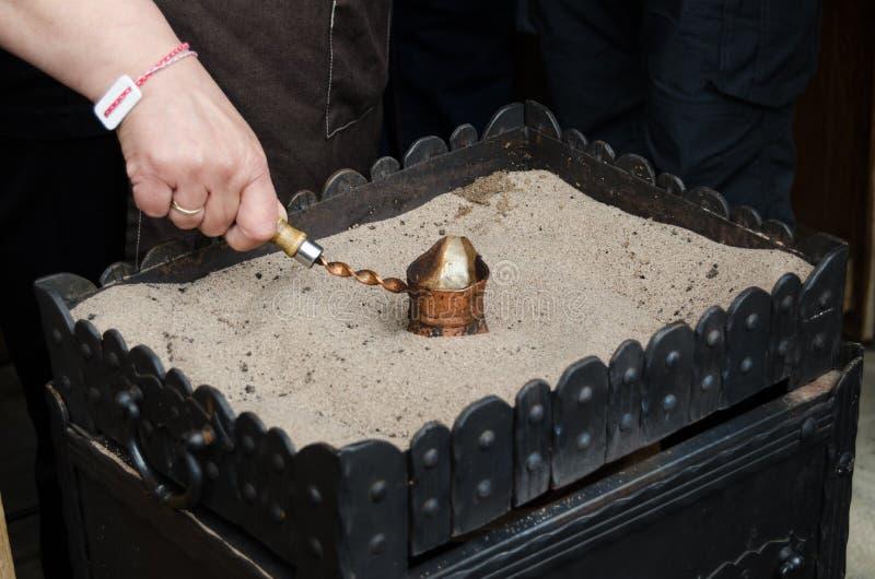Fermez-vous vers le haut de la vue du café turc préparée sur le sable d'or chaud Concept de préparation de café photos libres de droits