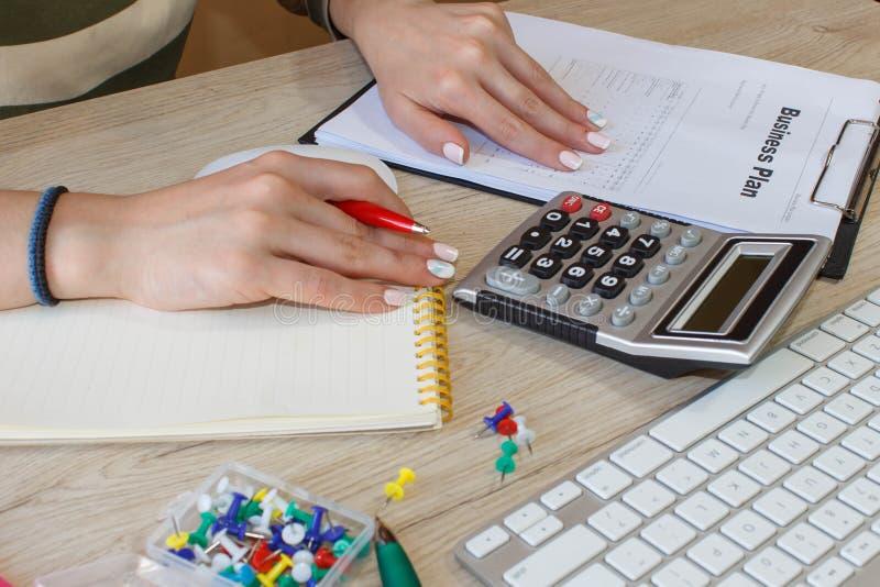 Fermez-vous vers le haut de la vue du comptable ou des mains financières d'inspecteur rédigeant le rapport, calculant ou vérifian image stock