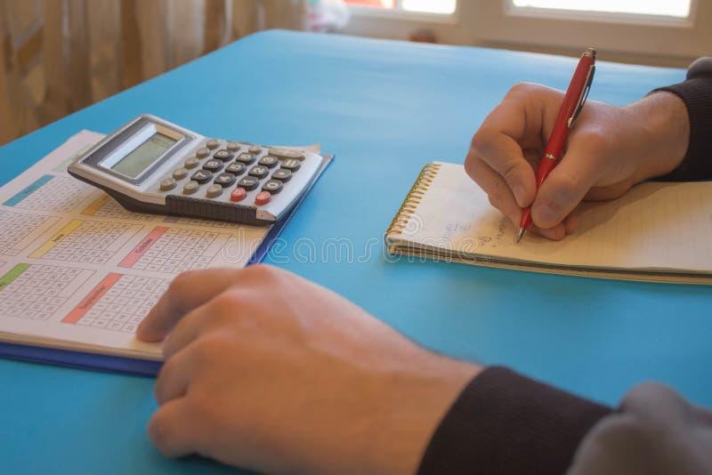 Fermez-vous vers le haut de la vue du comptable ou des mains financi?res d'inspecteur r?digeant le rapport, calculant ou v?rifian photo stock