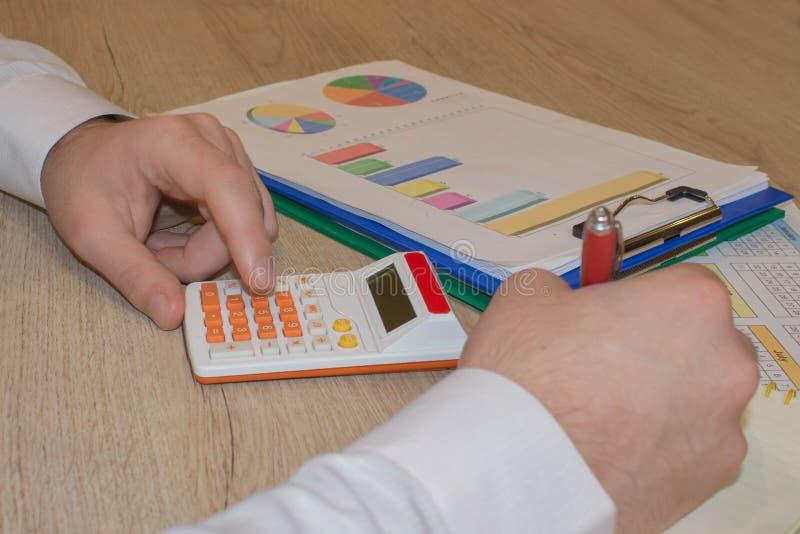 Fermez-vous vers le haut de la vue du comptable ou des mains financi?res d'inspecteur r?digeant le rapport, calculant ou v?rifian image libre de droits
