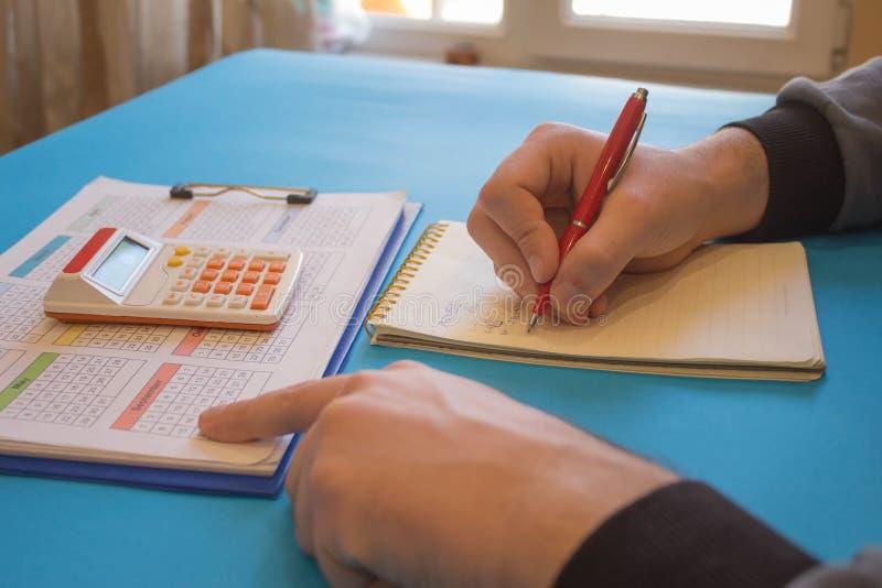 Fermez-vous vers le haut de la vue du comptable ou des mains financi?res d'inspecteur r?digeant le rapport, calculant ou v?rifian photos libres de droits