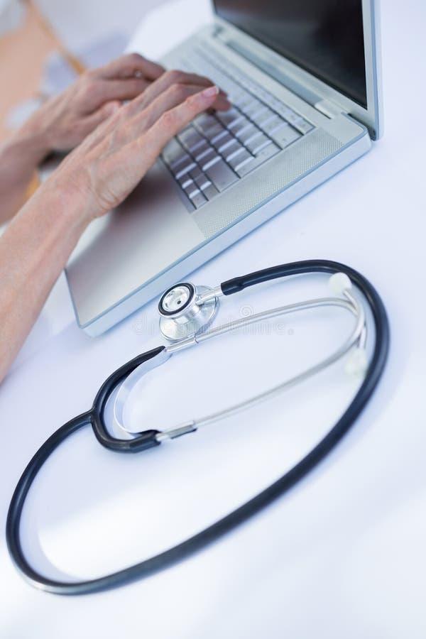 Download Fermez-vous Vers Le Haut De La Vue Du Docteur Féminin à L'aide De L'ordinateur Portable Photo stock - Image du bureau, partie: 56483922