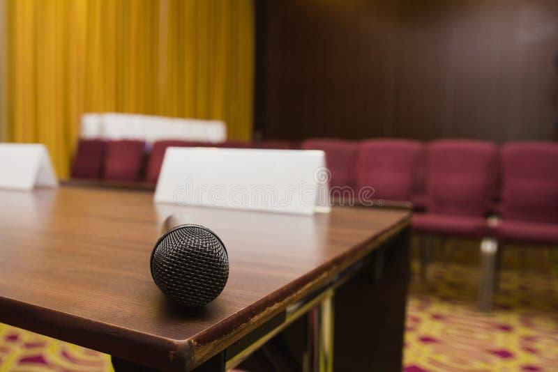 Fermez-vous vers le haut de la vue du microphone sur la table au fond de salle de conférences de presse ou de pièce de séminaire image libre de droits