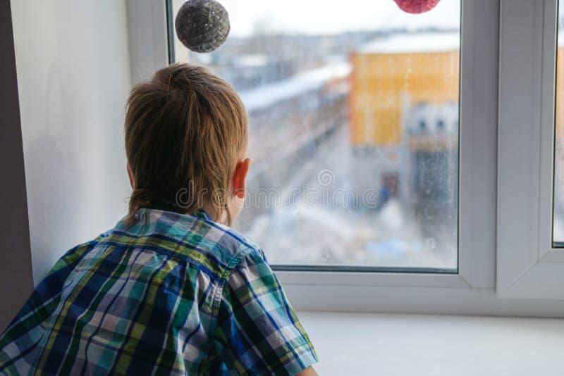 Fermez-vous vers le haut de la vue du petit garçon regardant hors de la fenêtre photographie stock