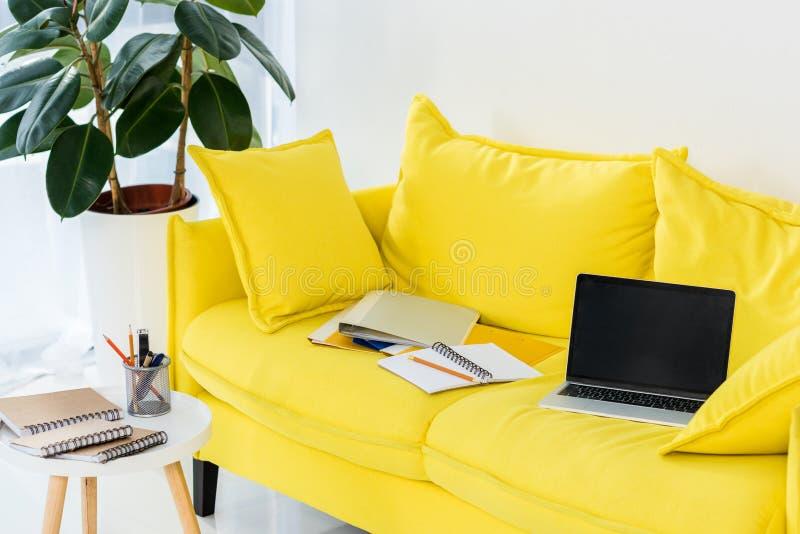 fermez-vous vers le haut de la vue de l'ordinateur portable, des carnets et des dossiers sur le sofa jaune photo libre de droits