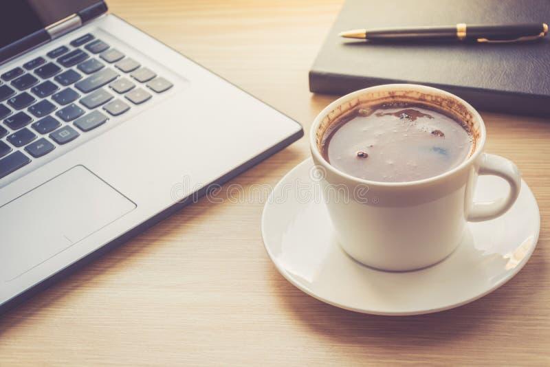 Fermez-vous vers le haut de la vue sur l'intérieur de bureau de travail avec la tasse d'ordinateur portable et de café de matin P photographie stock libre de droits