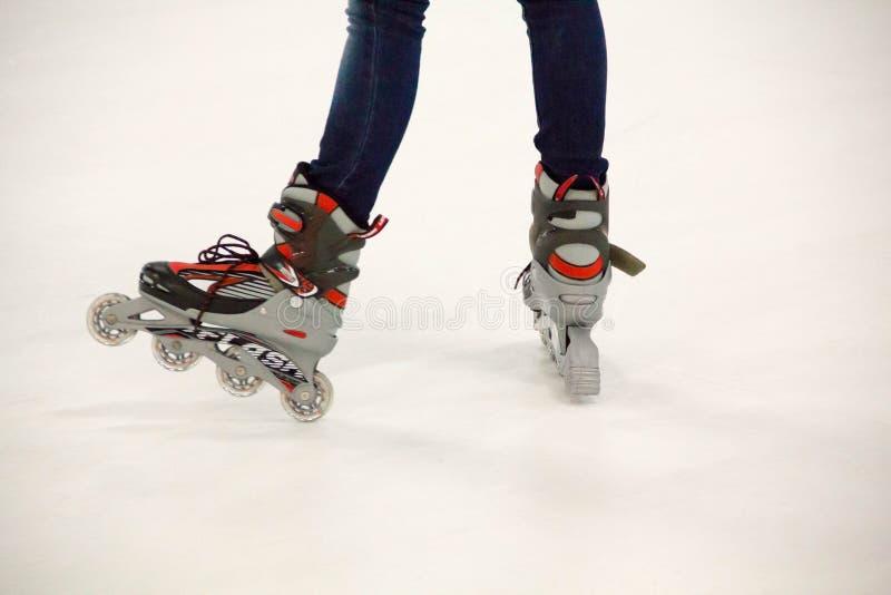 Fermez-vous vers le haut de la vue, sur le blanc, du patin intégré ou faites du roller sur la patinoire photo libre de droits