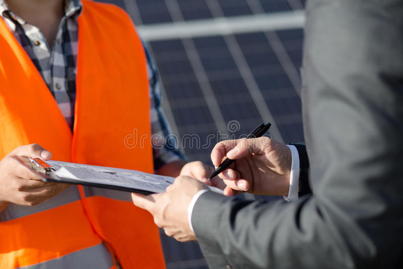 Fermez-vous vers le haut de la vue sur le contrat sigining d'agent de maîtrise et de client à la centrale solaire photo libre de droits