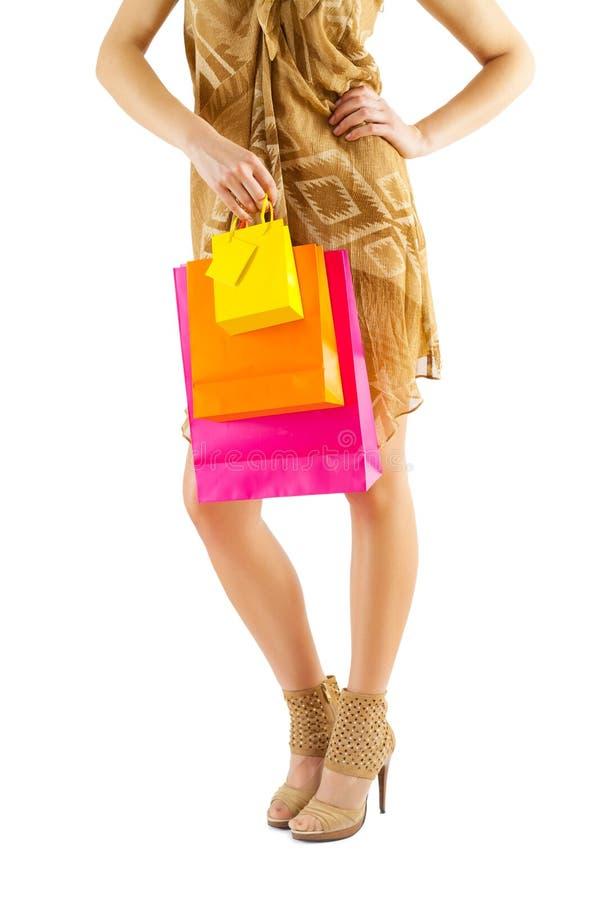 Fermez-vous vers le haut de la vue sur les jambes et les sacs en papier femelles à disposition photographie stock