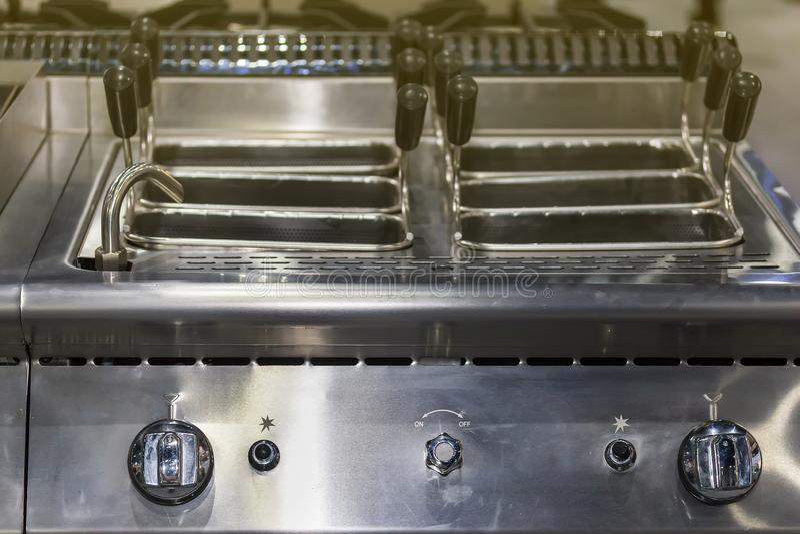 Fermez-vous vers le haut de moderne du contrôle profond de pot de friteuse de gaz et de cadran de bouton avec le panier inoxydabl image stock