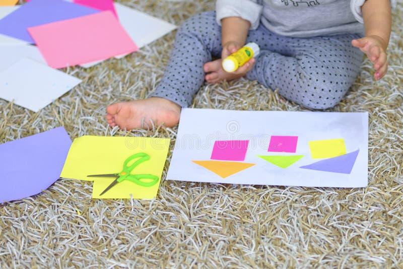 Fermez-vous vers le haut de peu de fille d'enfant en bas âge d'élève du cours préparatoire collant le papier coloré photo libre de droits