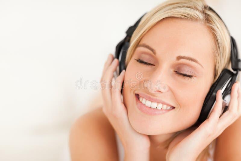 Fermez-vous vers le haut des écouteurs s'usants d'une femme sereine photographie stock libre de droits
