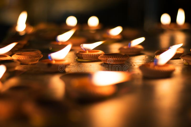 Fermez-vous vers le haut des ampoules ou de la bougie allumée pour adorer le Bouddha dans la nuit photos libres de droits