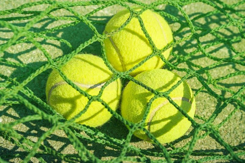 Fermez-vous vers le haut des balles de tennis sur le filet photographie stock libre de droits